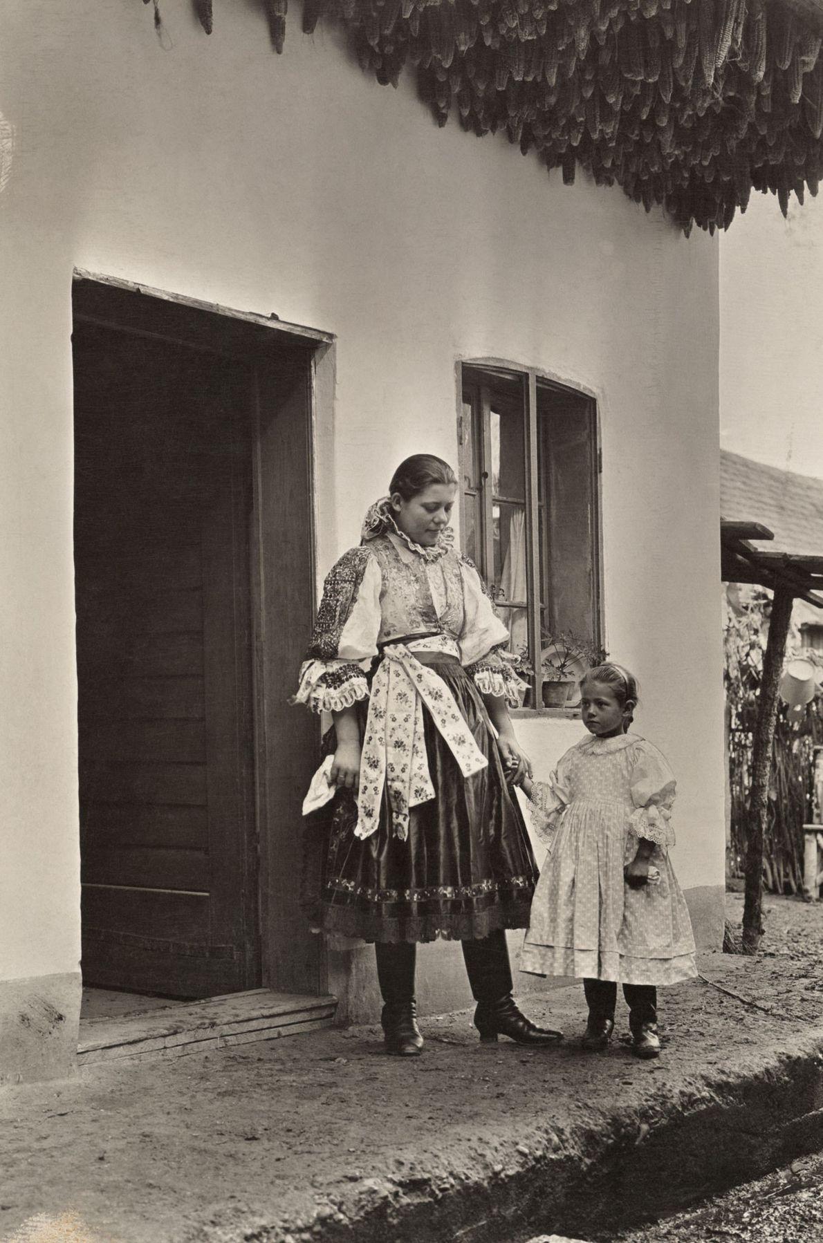 Uma mulher e a filha posam no alpendre de casa.