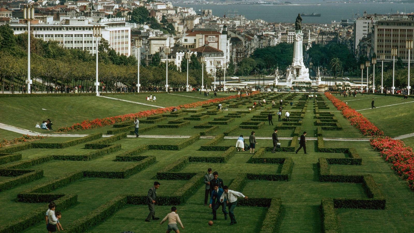 Várias pessoas passeiam pelos jardins esculpidos de um parque na cidade de Lisboa.