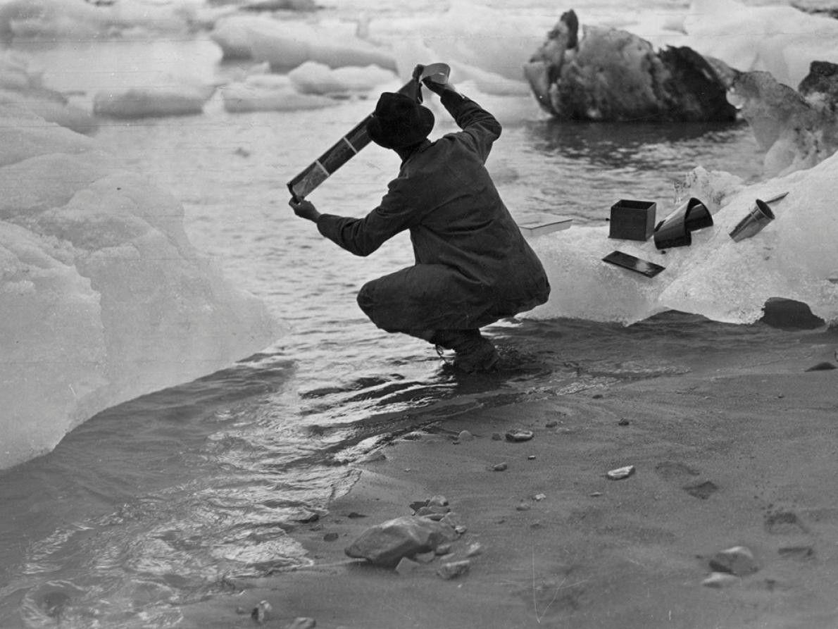 Fotógrafo agacha-se junto à margem da Baía Yakutat, Golfo do Alasca