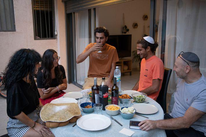 Uriel Herzberg (direita) e Isabelle Herzberg (esquerda) comemoram o seu primeiro jantar enquanto cidadãos israelitas com ...