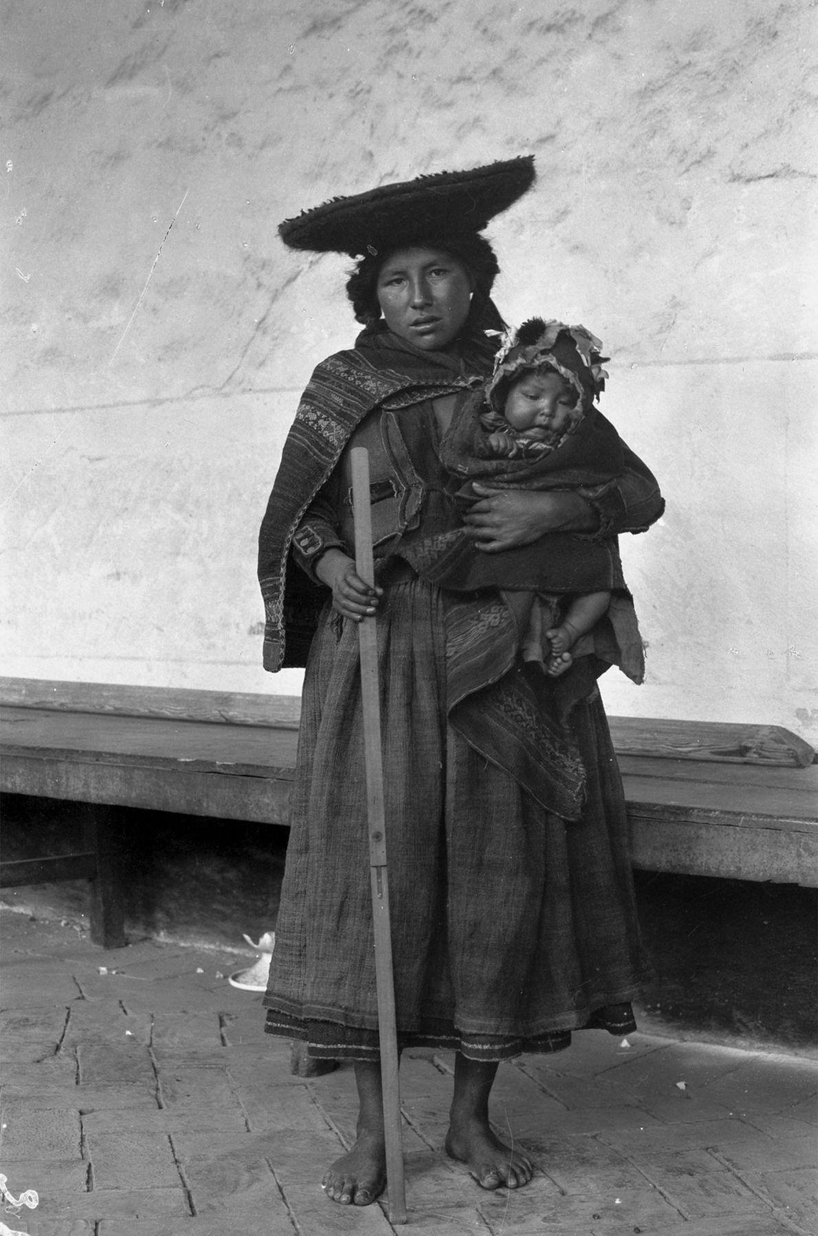 Uma mulher posa para a fotografia com um bebé ao colo.