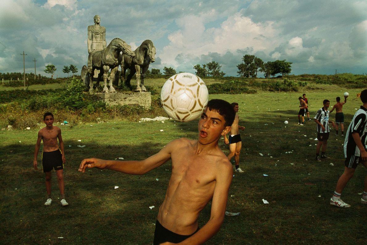 Um rapaz dá uns toques na bola com a cabeça.
