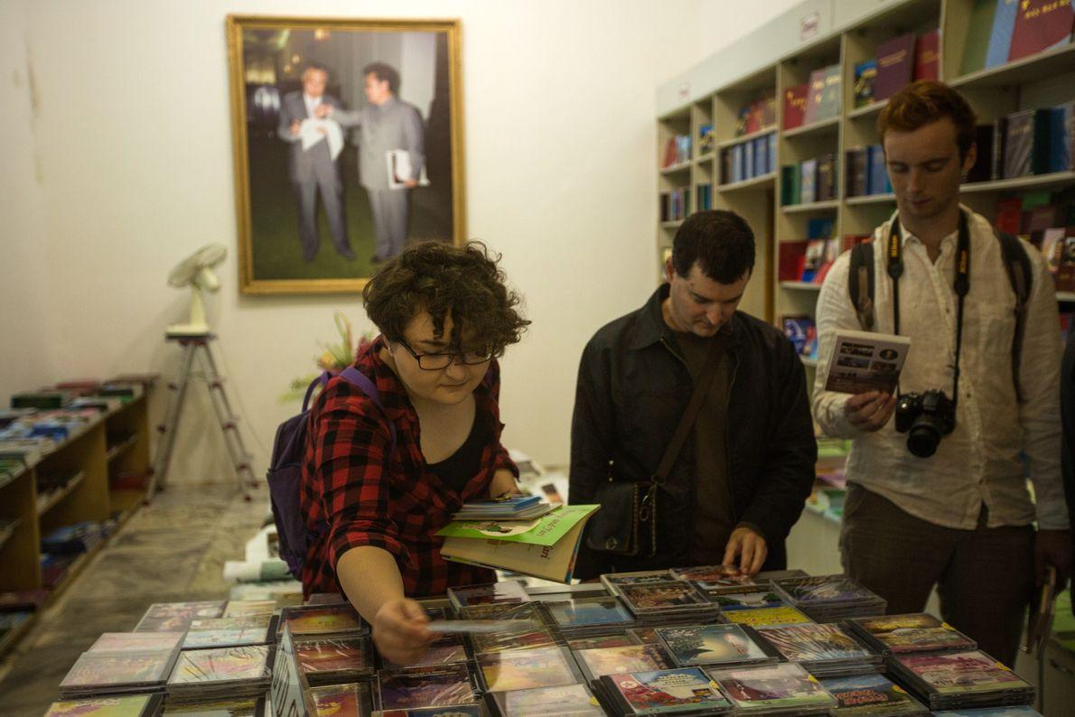 Uma livraria, com produtos em língua estrangeira, cheia de turistas que compram vários DVD de filmes ...