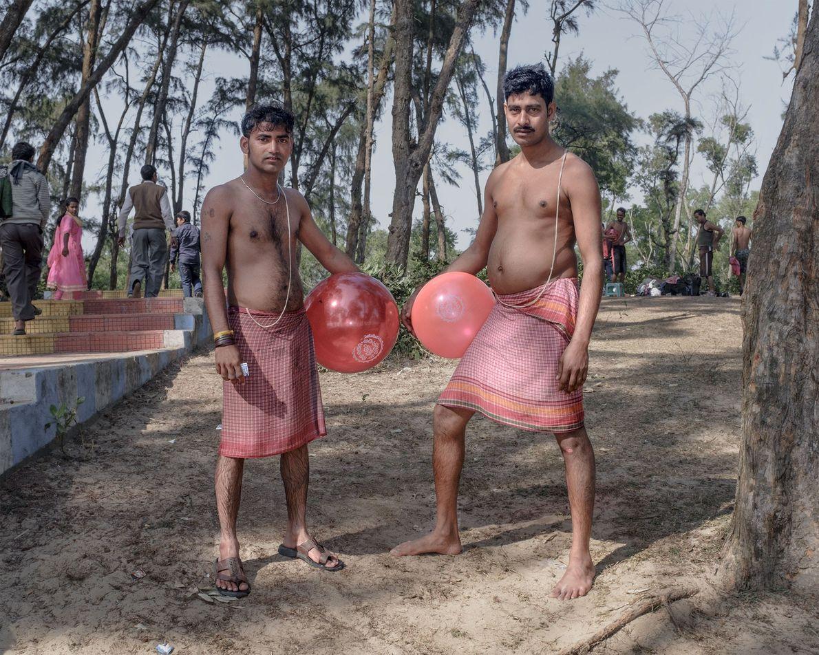 Dois homens seguram balões vermelhos na praia de Udaipur.