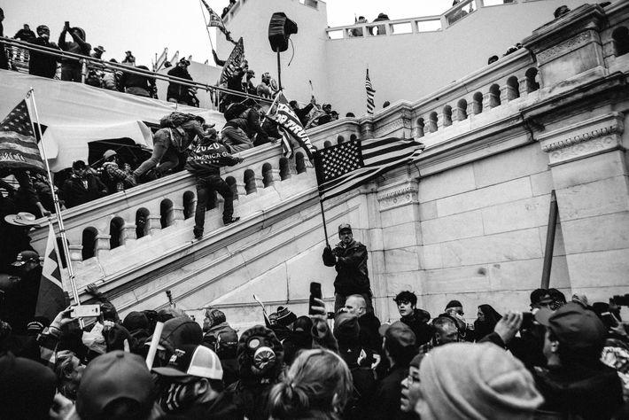 Apoiantes do presidente Donald Trump abrem caminho em direção aos degraus do edifício do Capitólio enquanto ...