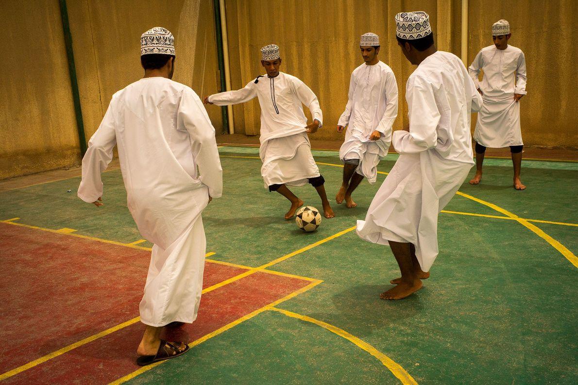 Um grupo de rapazes joga futebol de salão.