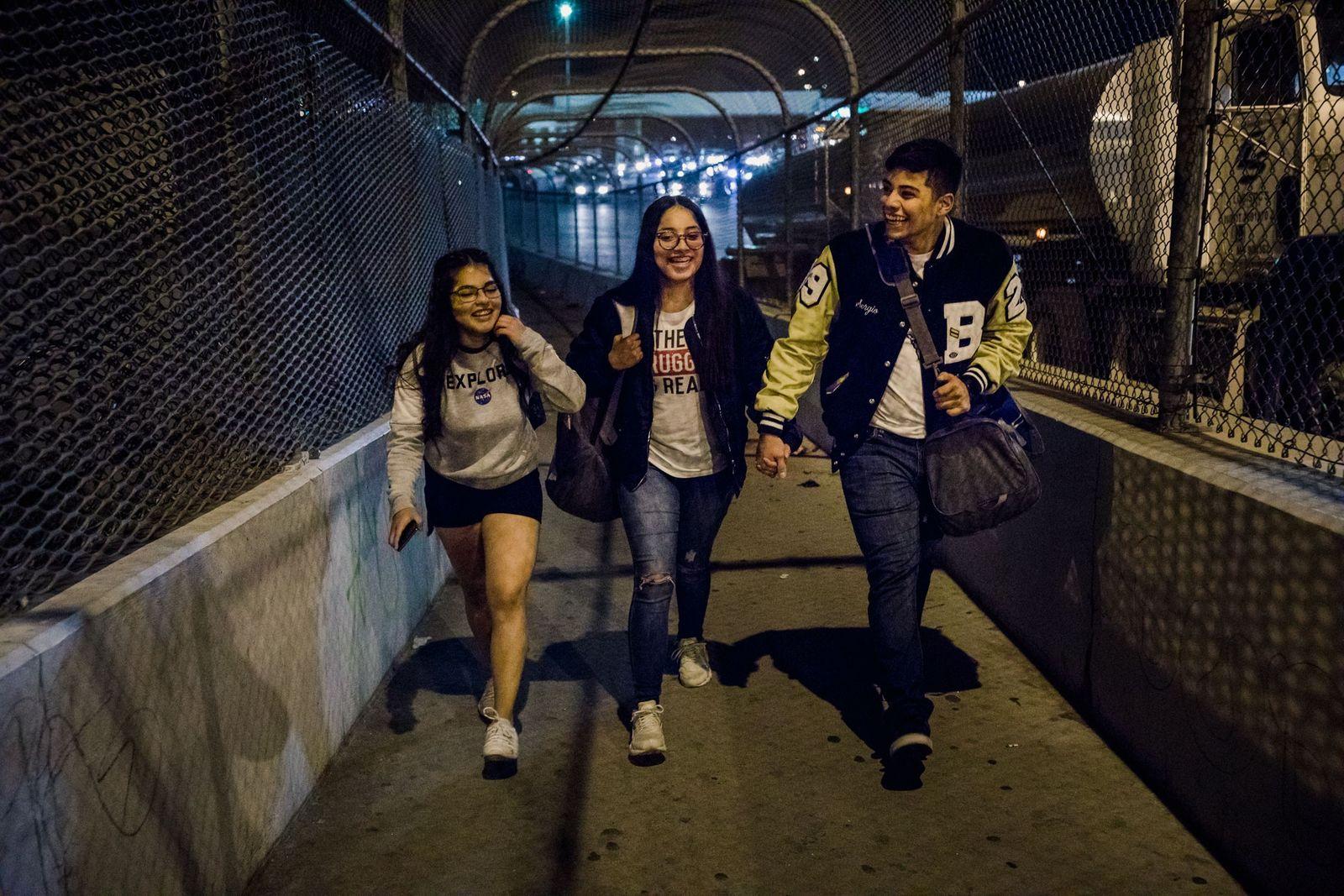 Ashley Esquivel, Megan Mejía e o namorado de Megan, Sergio Reyes, atravessam a ponte que liga ...