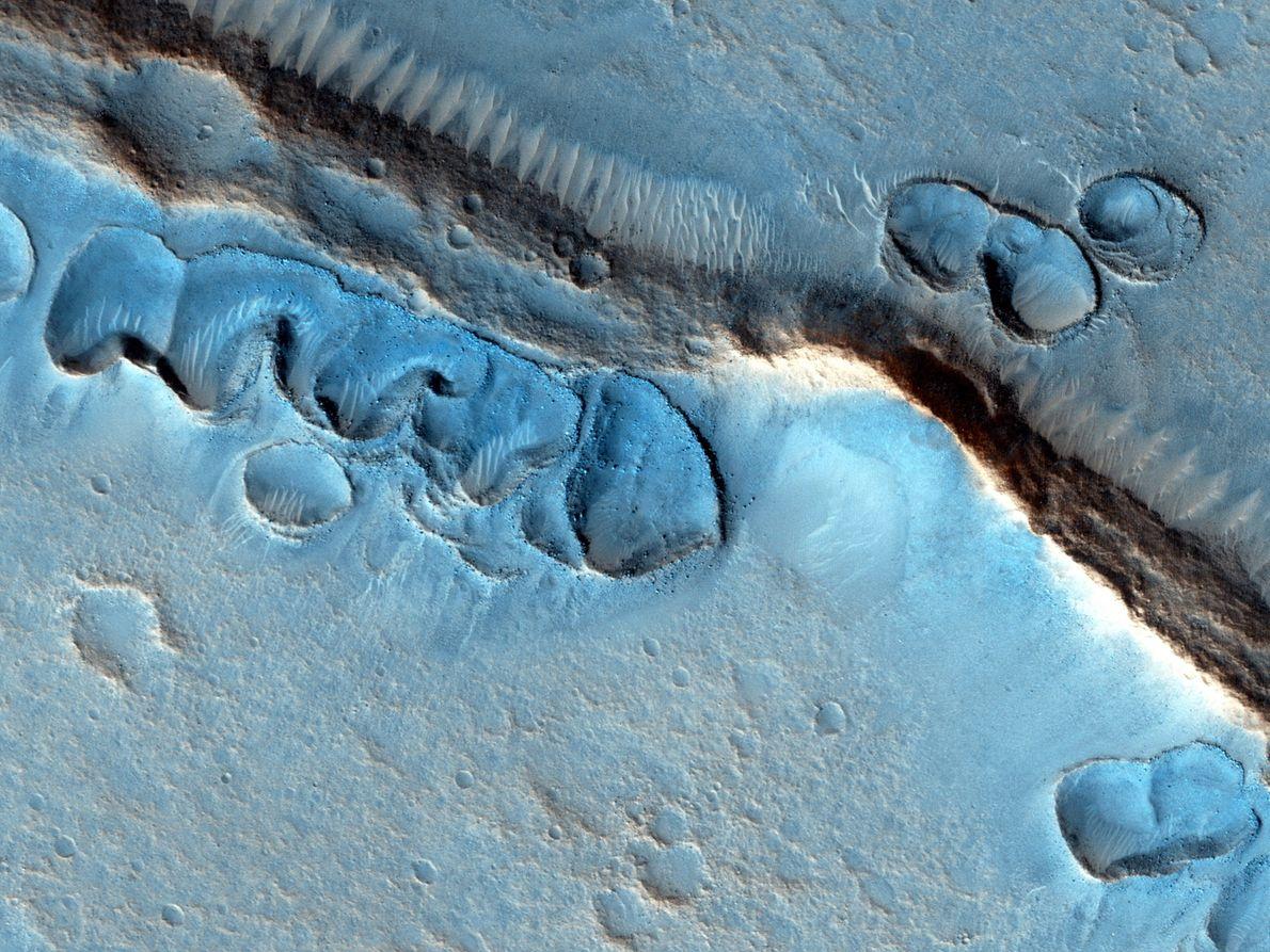Vários fossos superficiais, com formas irregulares e orlas elevadas.
