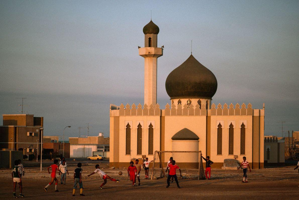 Um grupo de rapazes joga futebol em frente de uma mesquita.
