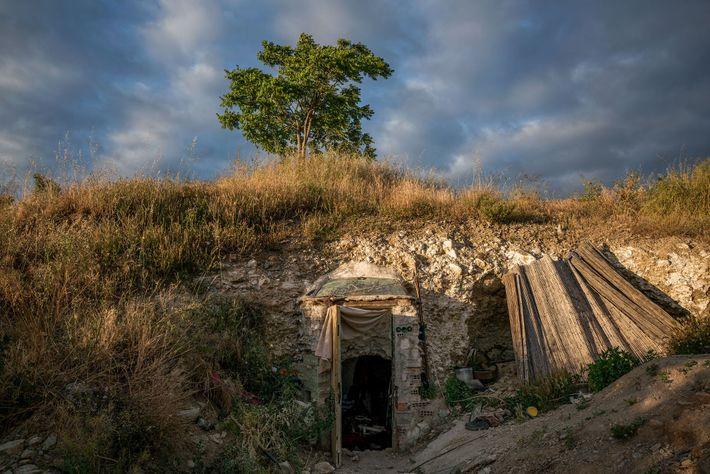 A porta da frente da gruta antecipa-se ligeiramente à parede rochosa em Sacromonte. Grande parte destas ...