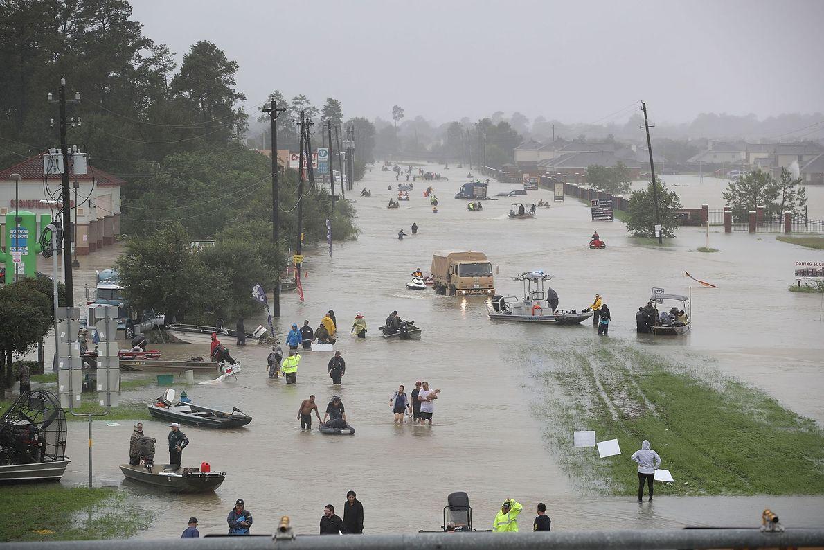 Pessoas a caminharem numa rua inundada de Houston