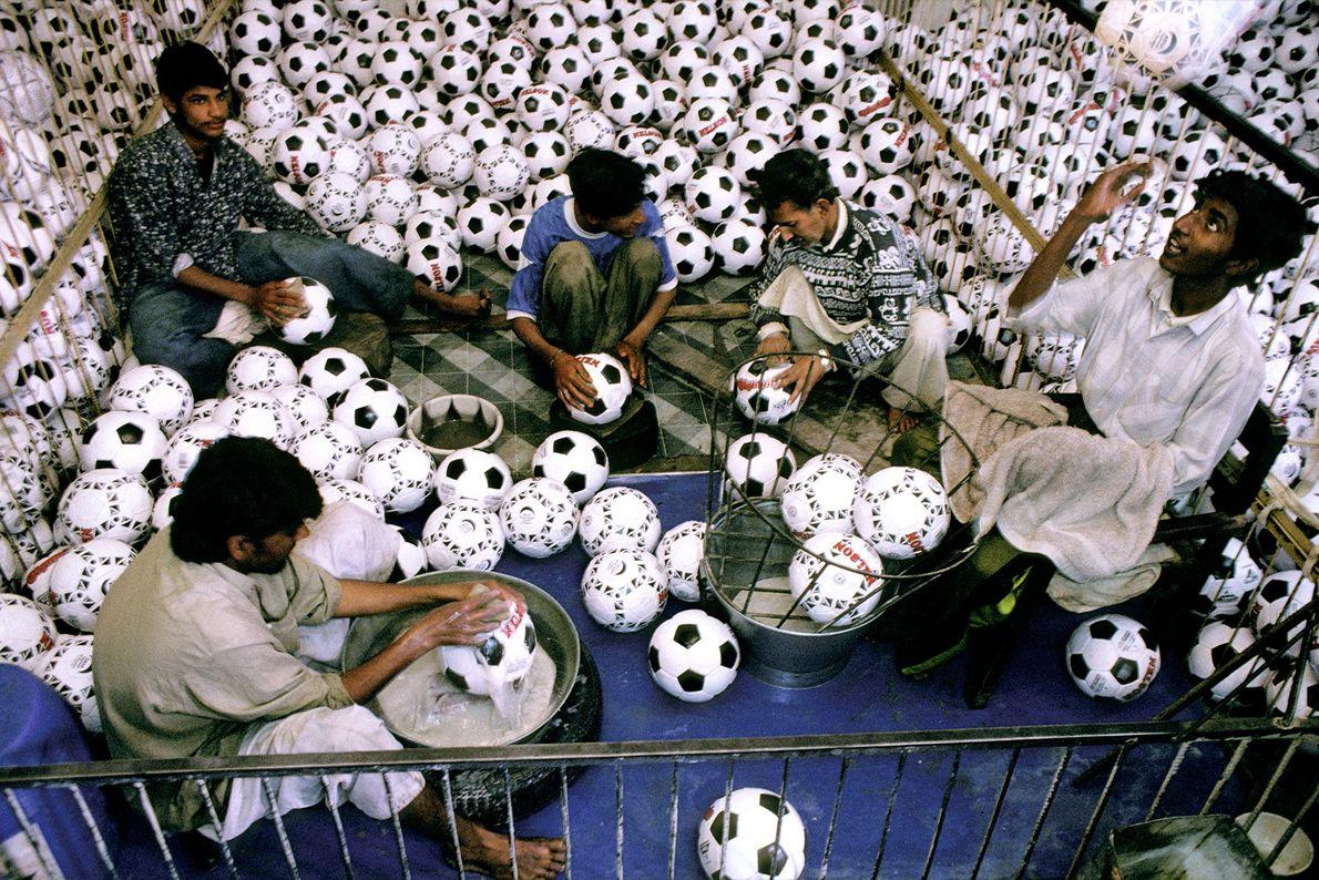 Jovens trabalhadores lavam bolas de futebol numa fábrica.