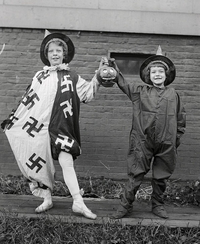 Raparigas mascaradas – incluindo uma com um traje coberto de suásticas – sorriem para a câmara ...