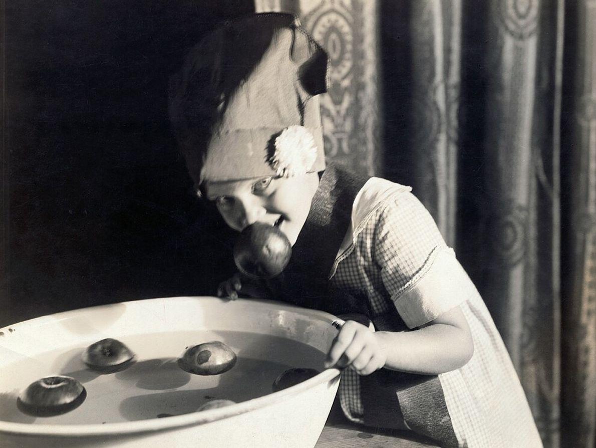 Uma menina norte-americana brinca com maçãs durante o Halloween, no início do século XX.  Devido às origens ...
