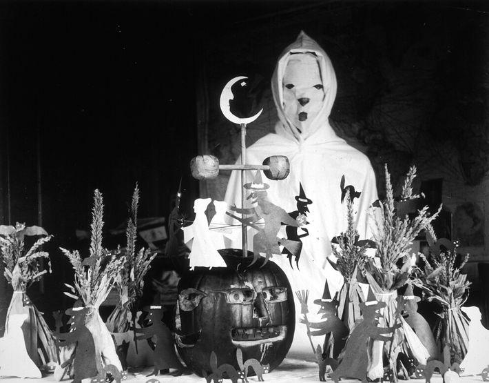 Uma pessoa vestida de fantasma junto a uma mesa com decorações de Halloween, numa escola rural ...