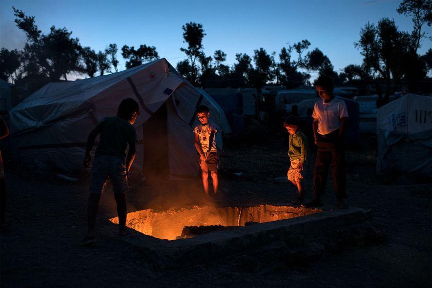 As crianças refugiadas reúnem-se em torno de um fosso, onde habitualmente é queimado lixo. A fogueira ...