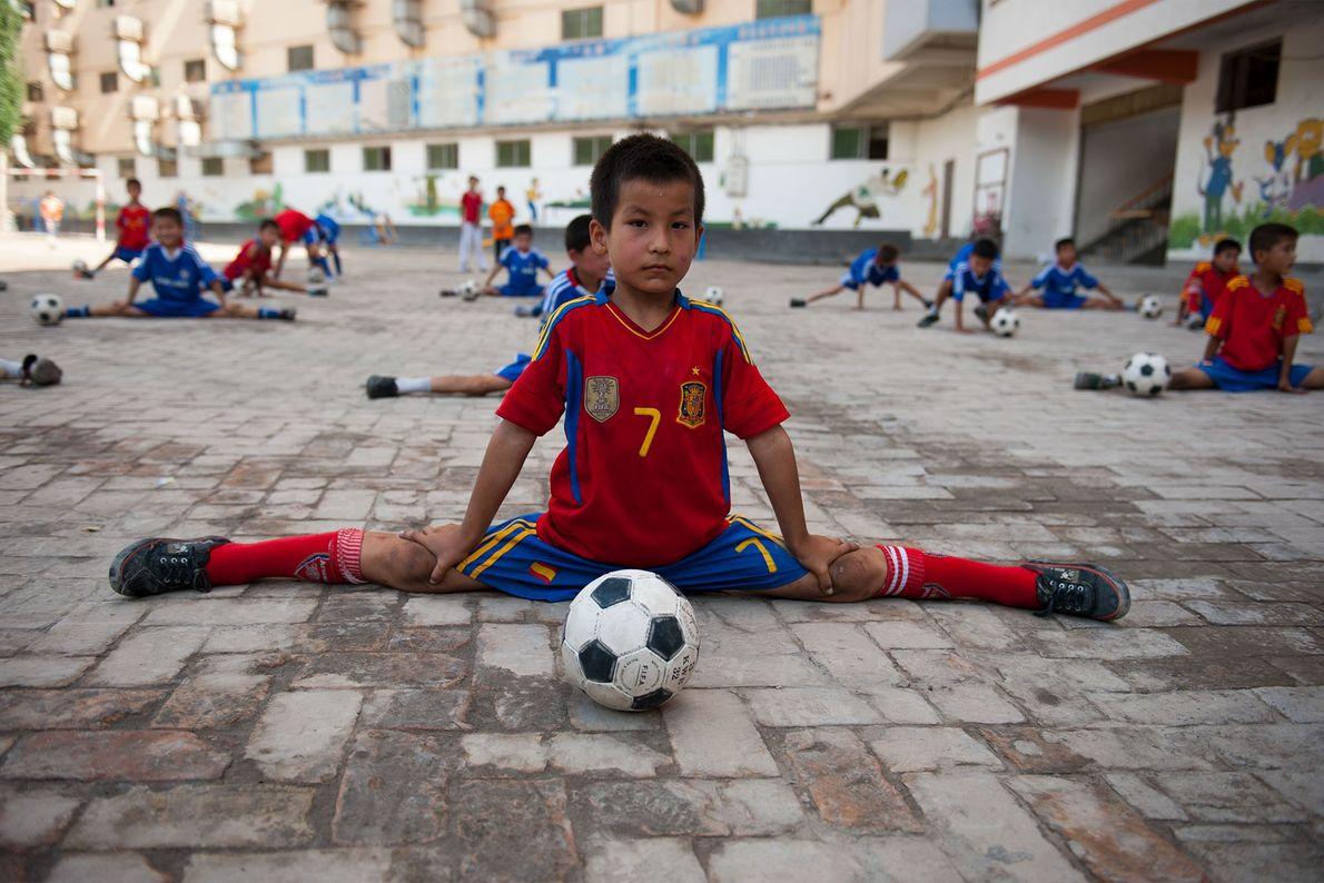 Um jovem jogador faz alongamentos.