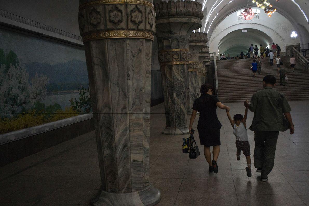Pessoas que estão em trânsito a brincar com os seus filhos em uma estação de metro ...