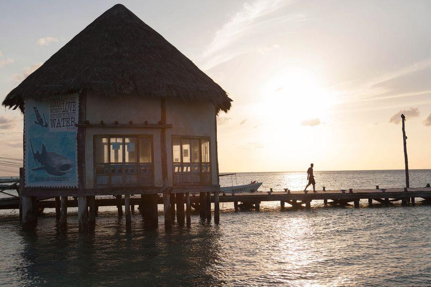 O pôr do sol visto do cais na Isla Holbox. Embora tenham sido propostos enormes projetos ...