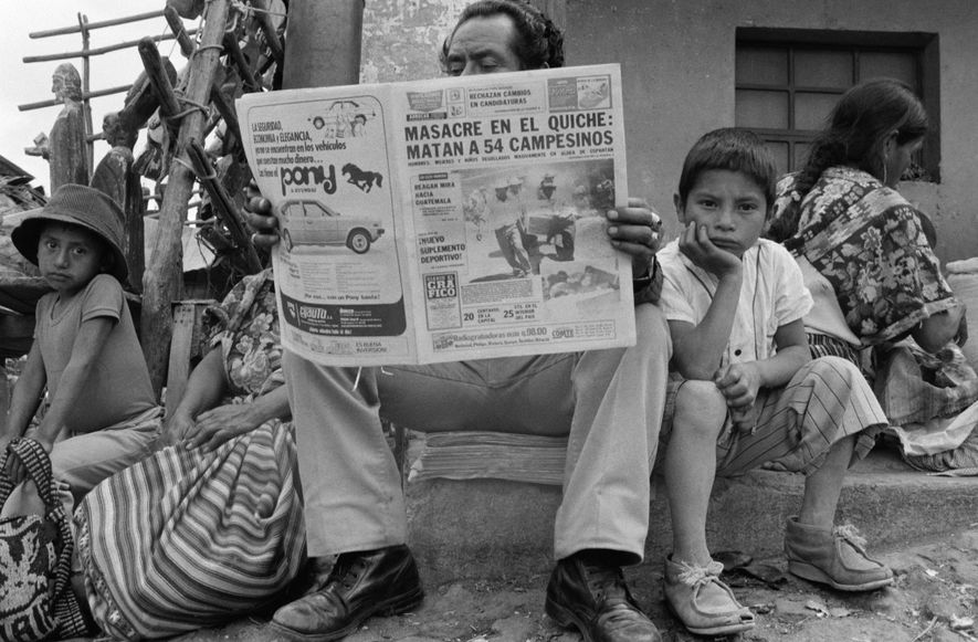 Um homem a ler um jornal sobre o massacre de 54 pessoas na região de Quiché, ...