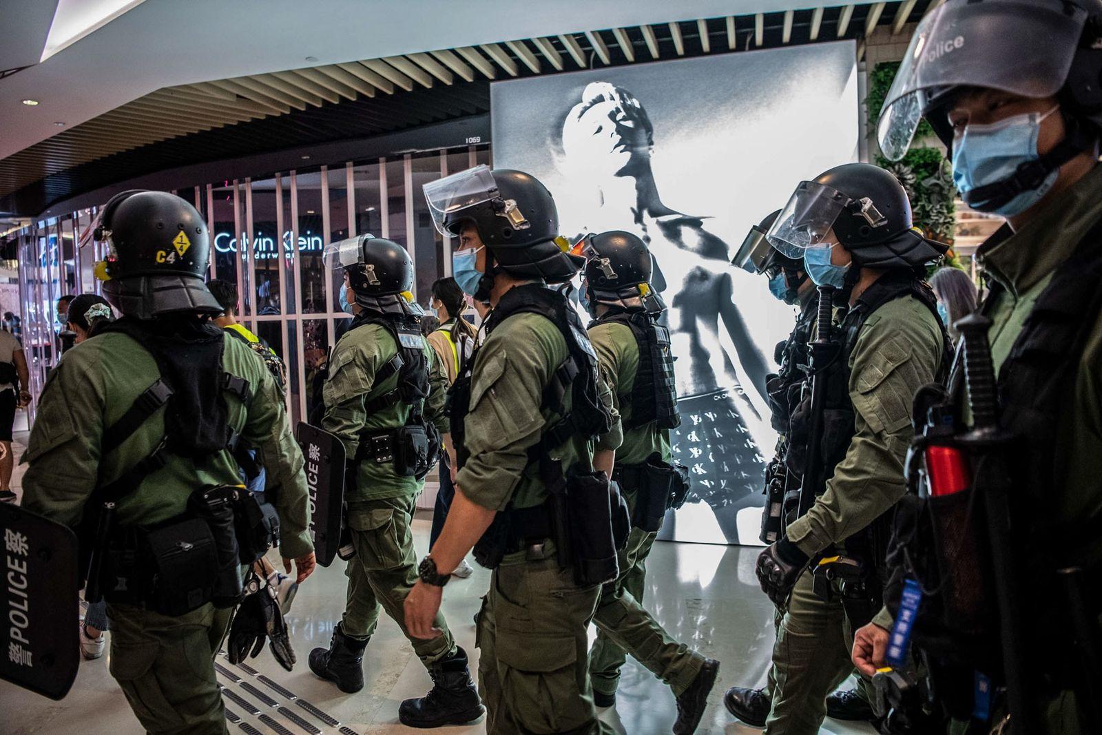 Forças da autoridade caminham pelo Centro comercial YoHo em Yuen Long, Hong Kong, no dia 21 ...