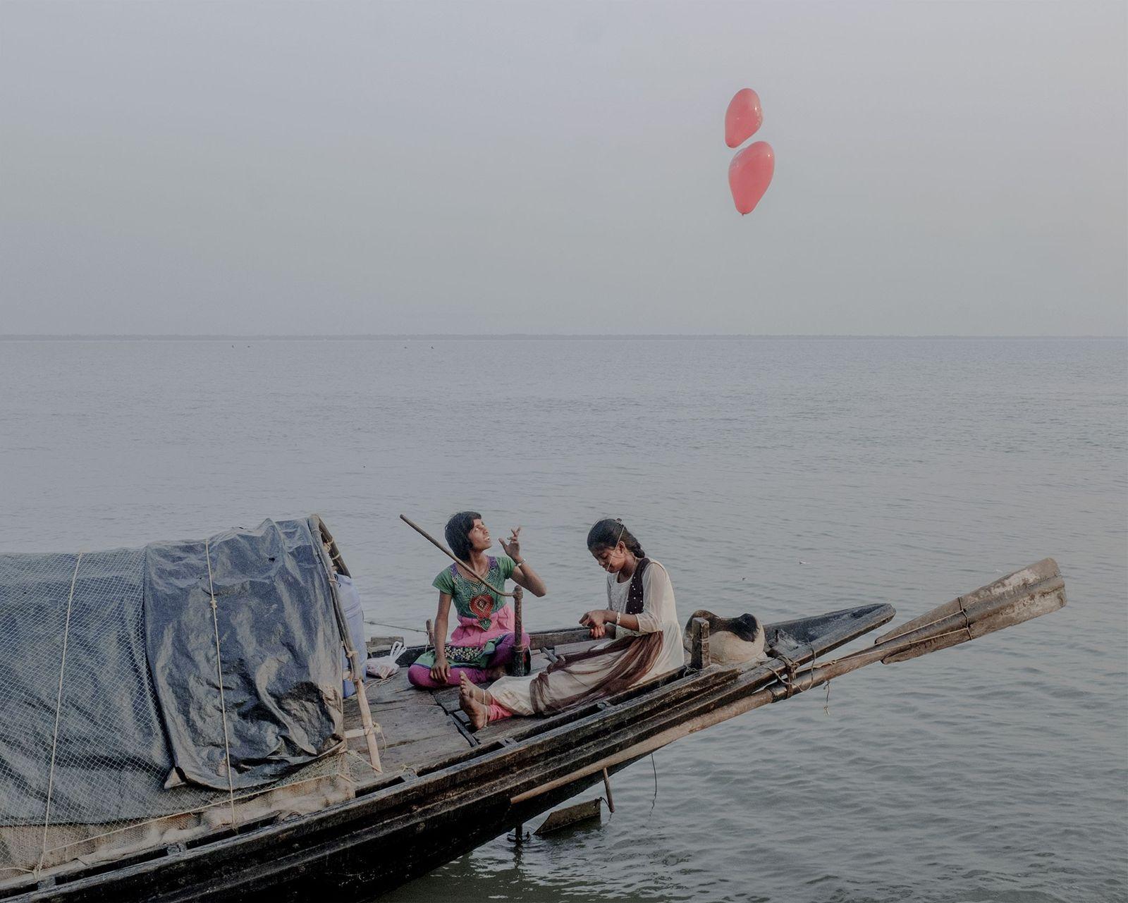 Duas mulheres navegam a bordo de uma embarcação.