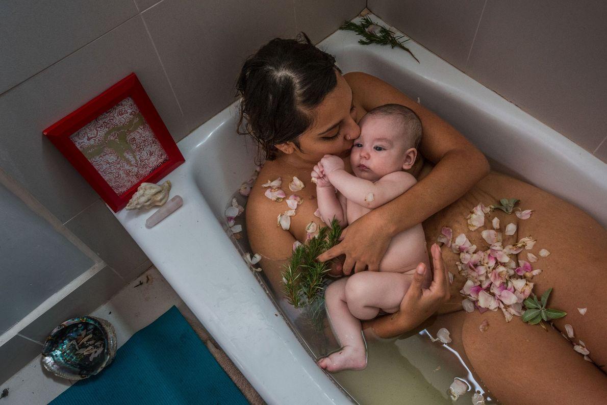 Mãe e filho celebram o fim do período de quarentena com um banho de ervas. Esta ...