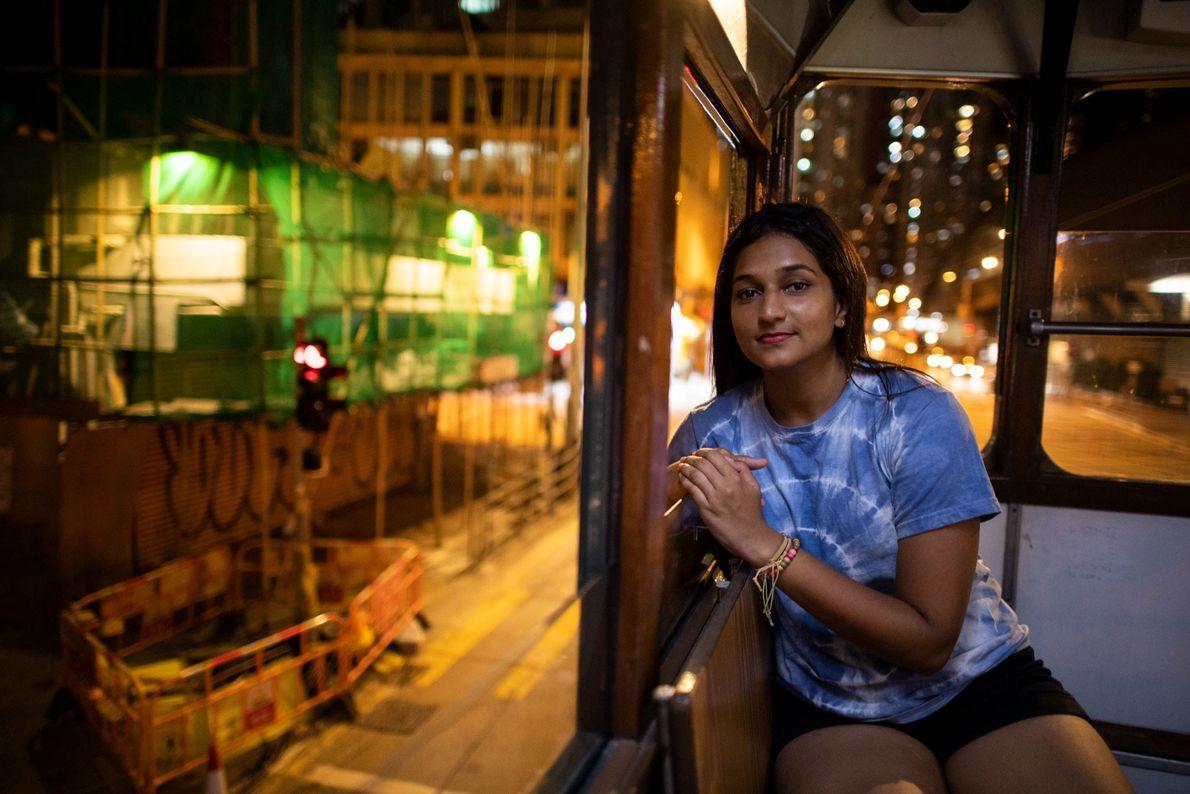 Deena Ravi Thinakaran, professora de 24 anos de descendência indiana, está sentada num elétrico em Sheung ...