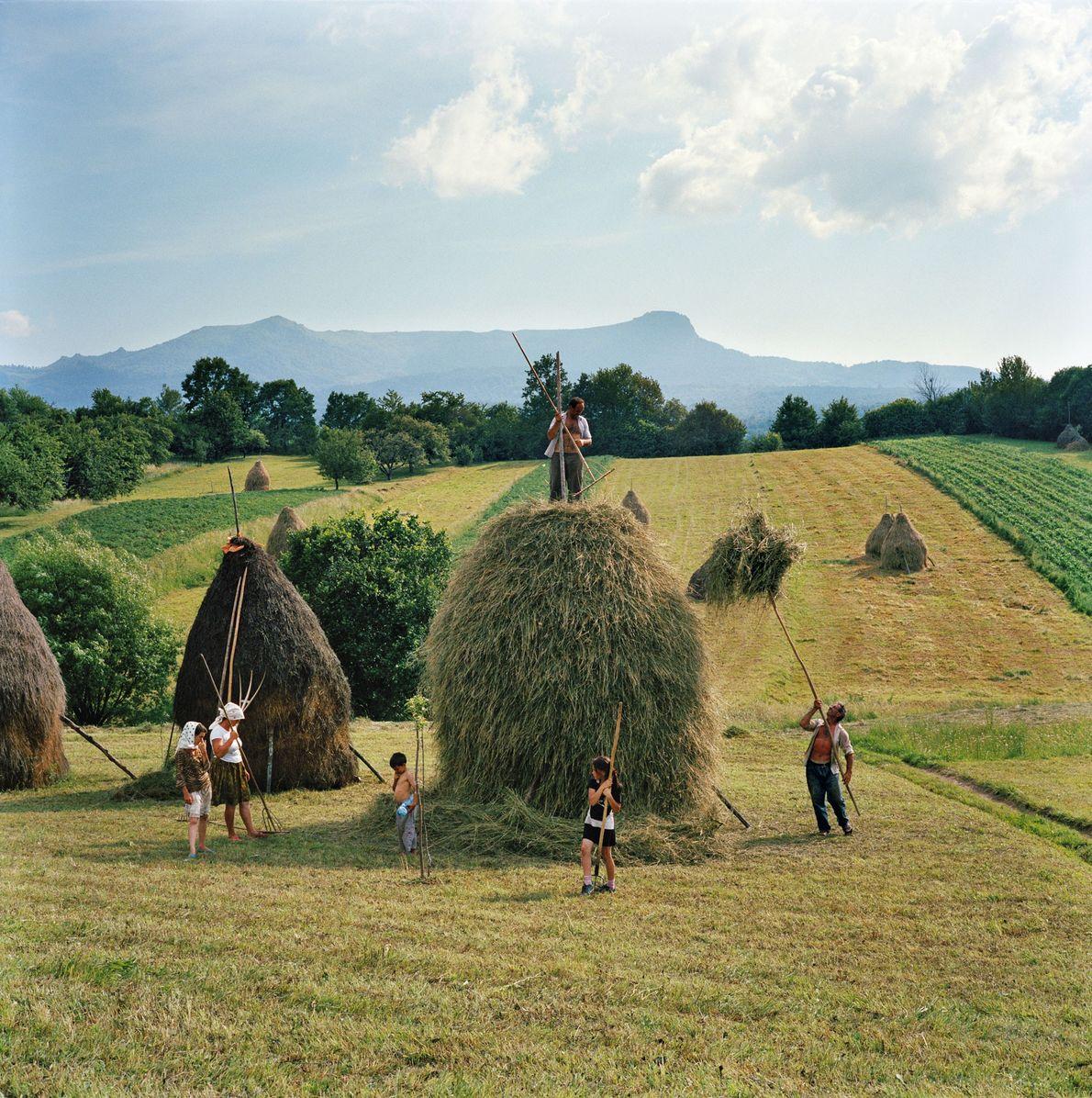 Uma família faz um monte de feno numa encosta de Breb, na Roménia.