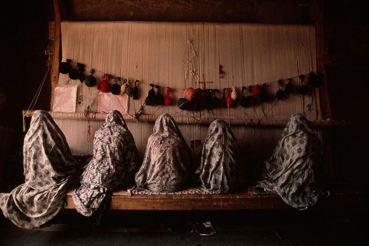 Uma família de mulheres iranianas a trabalhar com um tear. Estão a tecer tapetes para exportar.