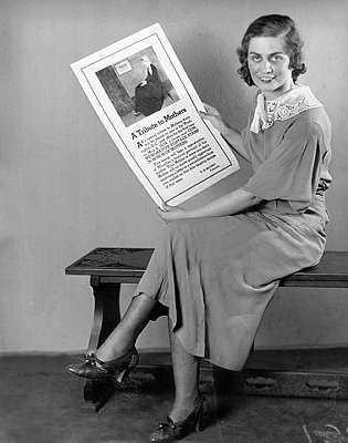 Mulher segura um poster de 1934 com publicidade ao selo do Dia da Mãe
