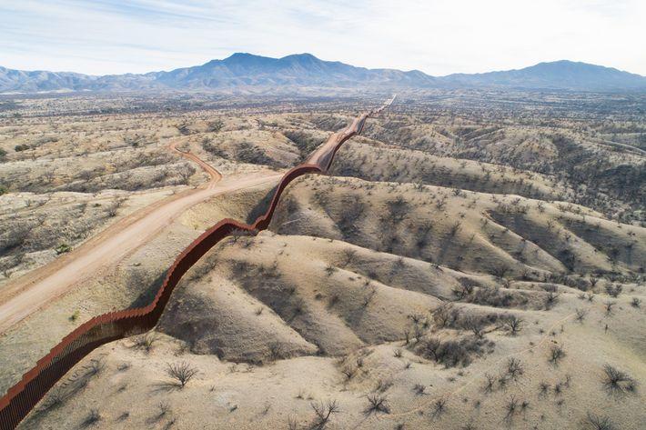 Uma vista aérea do lado mexicano do muro fronteiriço, a leste de Nogales, com as montanhas ...