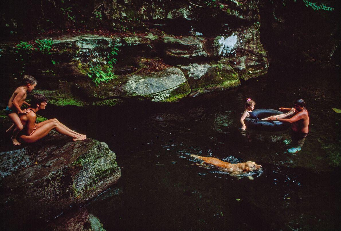 Veraneantes nadam com o seu cão no rio Neversink, nas Montanhas Catskill, em Nova Iorque.