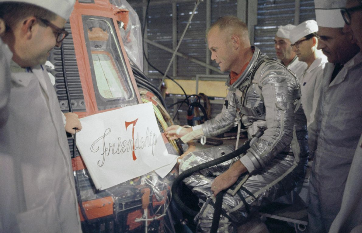 "O astronauta John Glenn examina o logótipo para o nome ""Friendship 7"" que iria ser pintado ..."