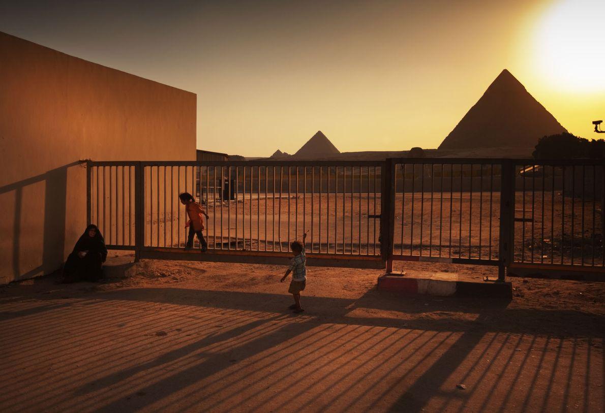 Crianças brincam nos portões exteriores das Pirâmides de Gizé