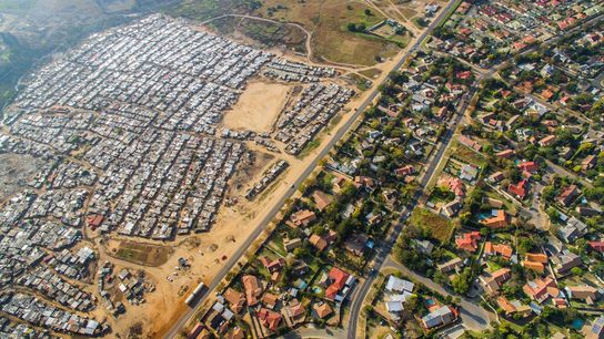 A neighborhood with green lawns and bright swimming pools borders a field of tin shacks in ...
