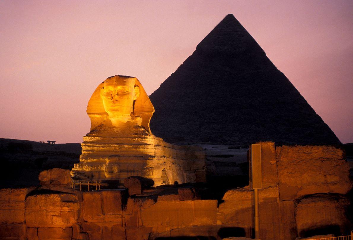As pirâmides e a esfinge à noite, em Gizé, no Egito