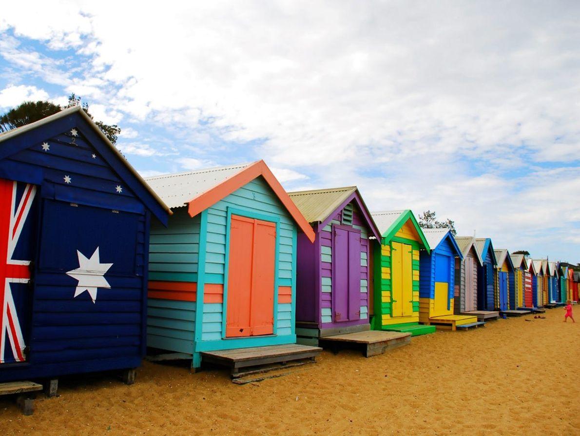 Barracas de praia coloridas alinham-se no areal da Praia de Brighton