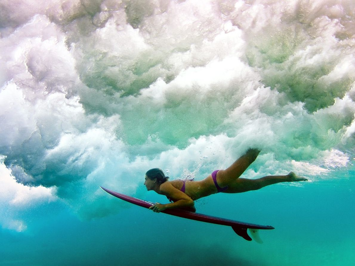 A surfista de longboard australiana Belinda Baggs mergulha sob uma onda