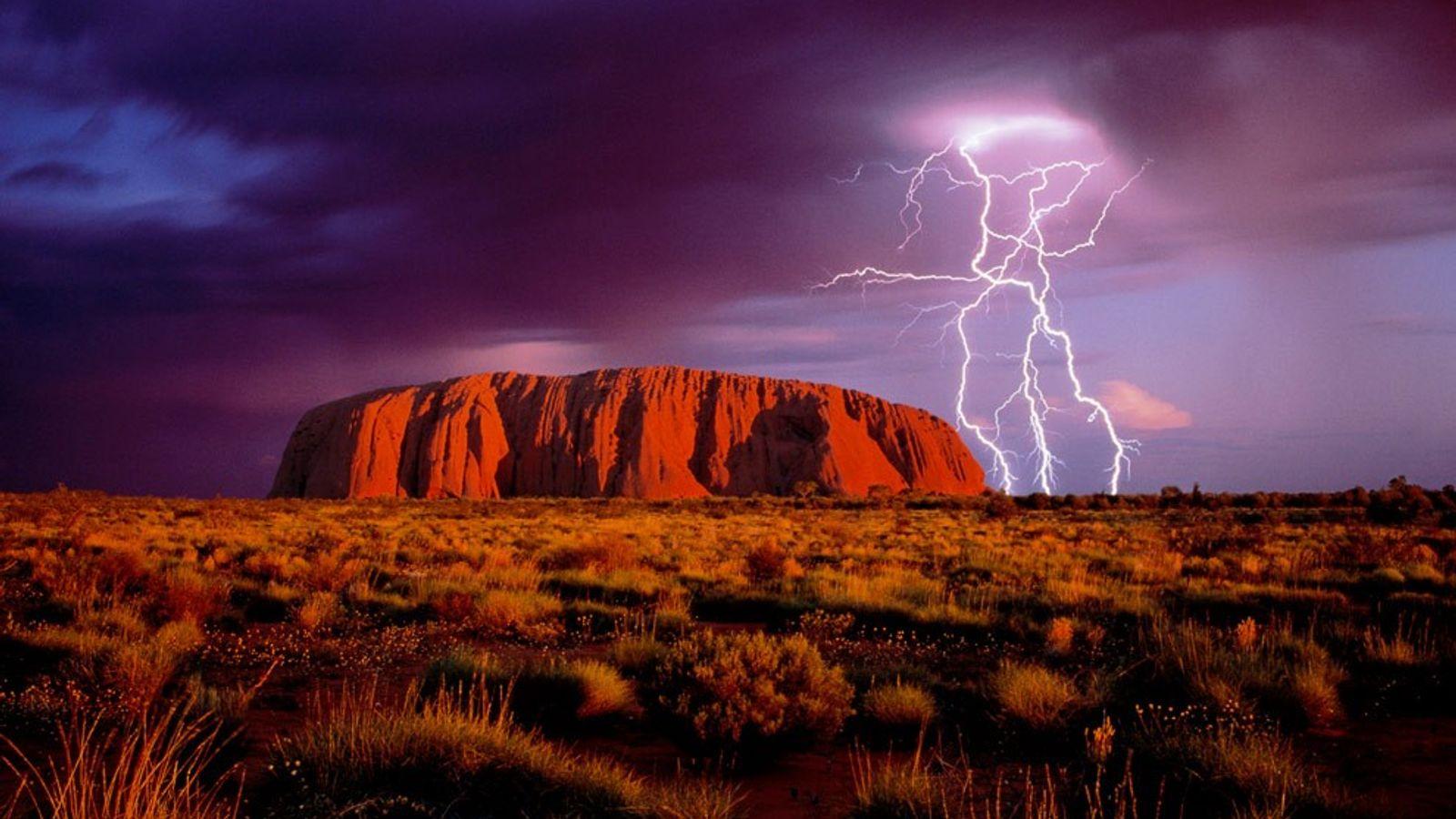 Relâmpagos lampejam sobre Ayers Rock, um monólito de arenito vermelho e um dos principais símbolos australianos