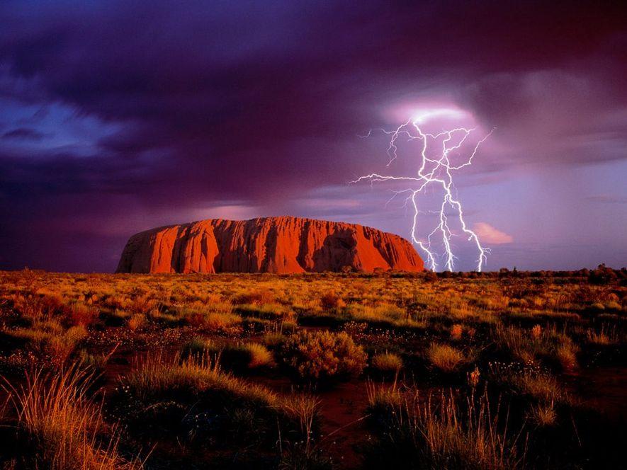 Relâmpagos lampejam sobre Ayers Rock, um monólito de arenito vermelho e um dos principais símbolos australianos, ...