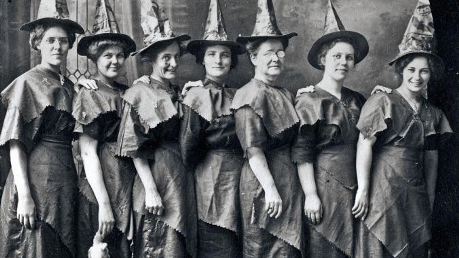 """Uma assembleia de """"bruxas"""" mascaradas juntas para um retrato de Halloween, por volta de 1910."""