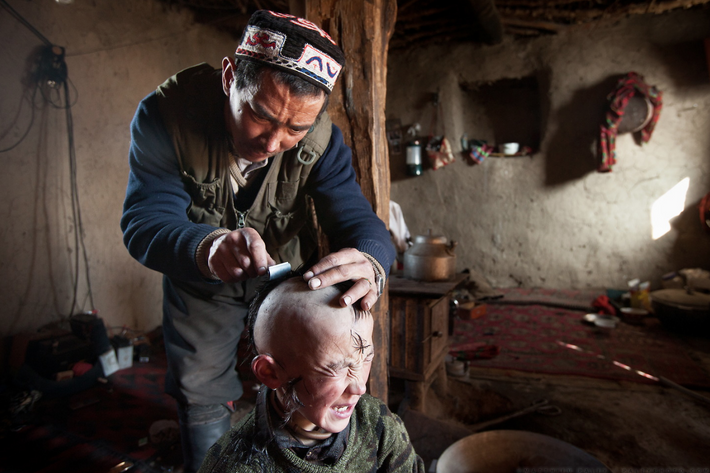 Fotografia de homem a rapar o cabelo a uma criança