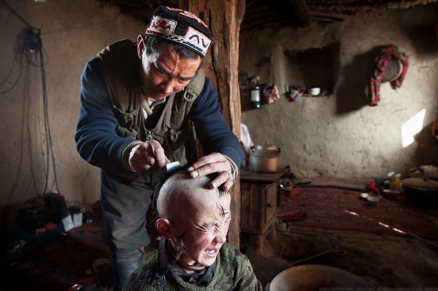 Fotografia de um homem a rapar o cabelo a uma criança, numa comunidade isolada