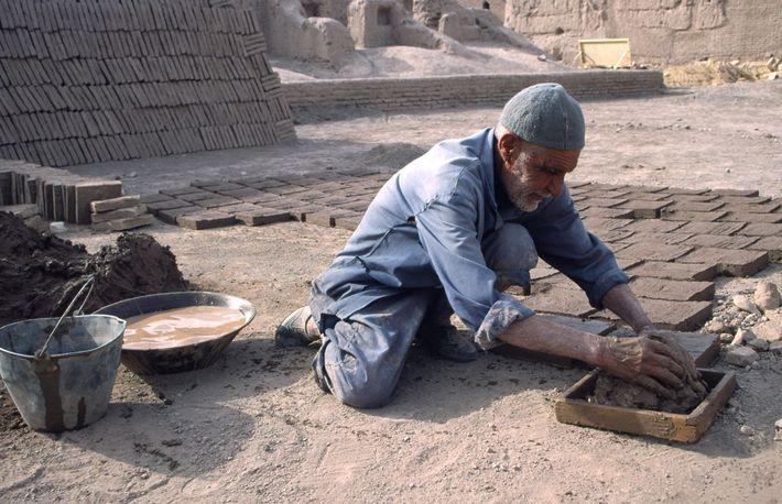 Um homem prepara um tijolo de lama seco ao sol