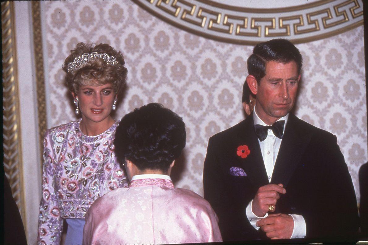 Diana e Carlos cumprimentam uma pessoa não identificada