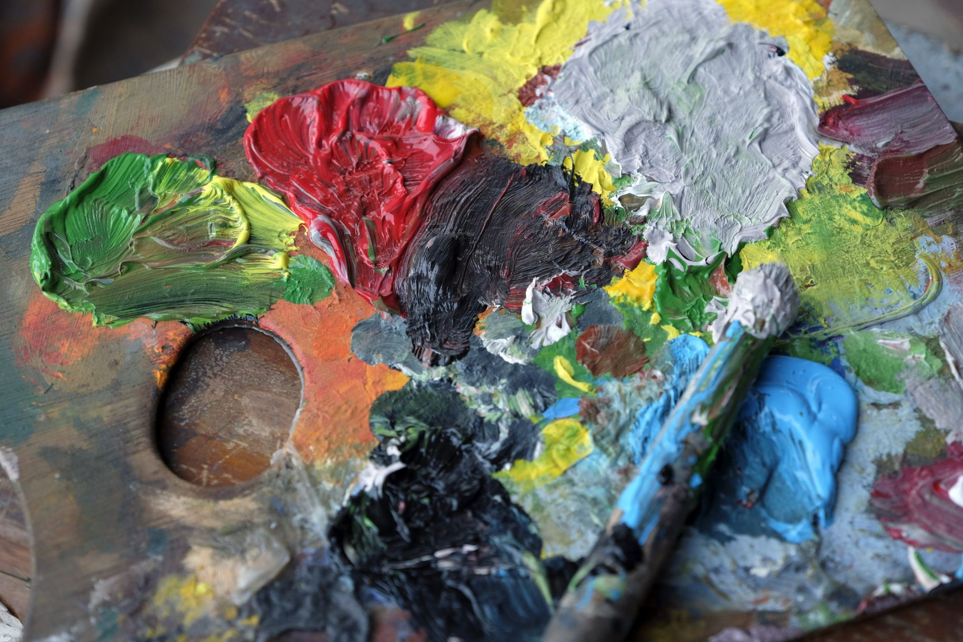 Paleta com mistura de tintas e pincel.