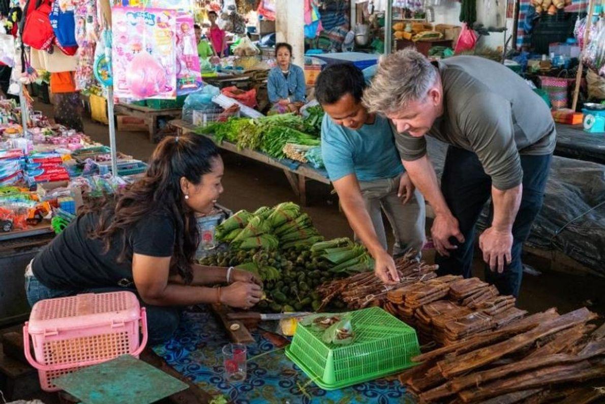 O chef Joy Ngeuamboupha guia Gordon Ramsay num mercado no Laos para comprar ingredientes para a ...