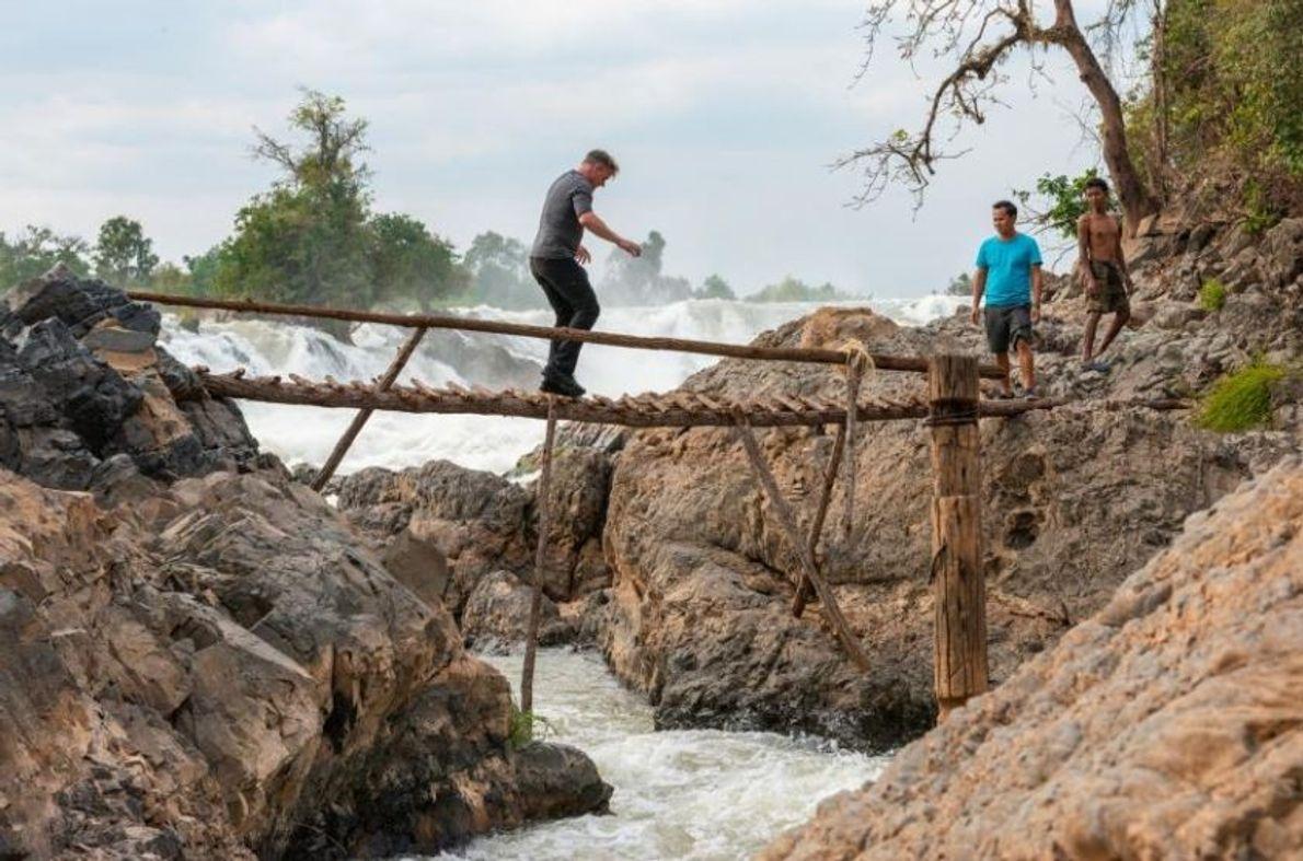 O chef Joy Ngeuamboupha e um pescador local esperam que Gordon Ramsay atravesse um passadiço de ...
