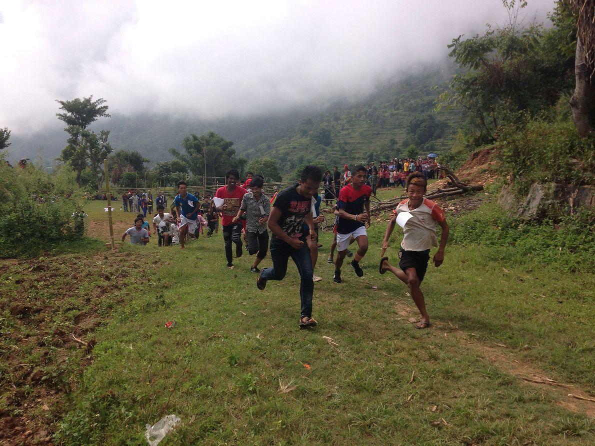 Imagem dos aldeões locais que participam numa corrida na aldeia natal da Mira Rai, no Nepal.